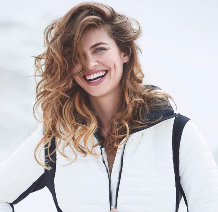 Uśmiechnięta kobieta w kręconych włosach