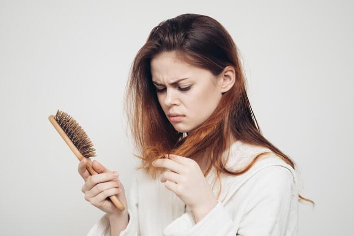 Kobieta zaskoczona wypadającymi włosami widocznymi na szczotce